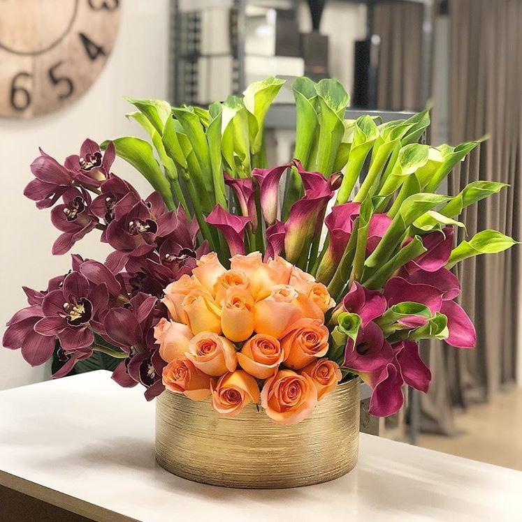Modern Gold Container Flower Arrangement with cranberry calla lilies, green goddess calla lilies, burgundy cymbidium orchids and peach roses