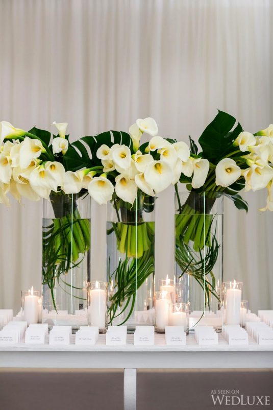 White Calla Lilies, Monstera Leaves and Beargrass Card Table Flower Arrangement by Forget Me Not of Oakville on wedluxe.com