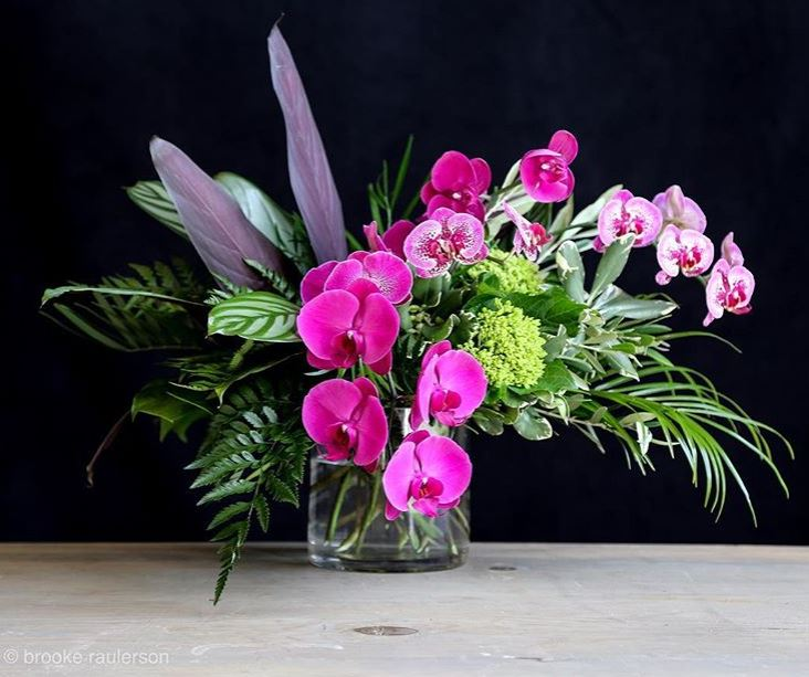 Hot Pink Tropical arrangement by Revelation Design with orchids, hydrangea & palms